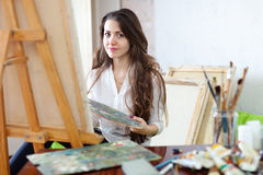Long-haired  artist paints picture on canvas Royalty Free Stock Photo