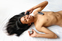Long-haired Asian boy with 3 cell-phones. Stock Photo
