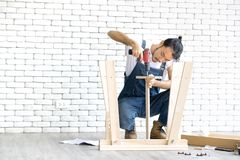 The long-haired Asian carpenter was deliberately assembling a wooden table with a drill in the office there is white brick block. royalty free stock photography