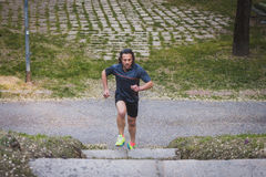 Long haired athlete running in a city park Royalty Free Stock Photography