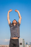 Long haired athlete stretching against blue sky Royalty Free Stock Images