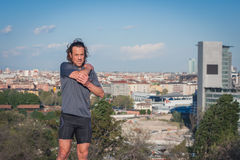 Long haired athlete stretching in a city park. Mature long haired athlete stretching in a city park Royalty Free Stock Photography