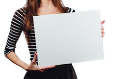 Long-haired beautiful cute brunette woman holding a rectangular blank-poster. white canvas with space for text. Stock Photos
