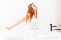 Long-haired beautiful woman waking in her bed at home Stock Photo