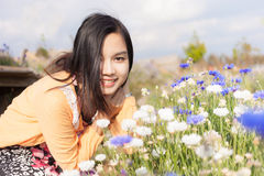 Long haired black asia girl happy smile in the flowers garden Stock Images