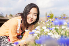 Long haired black asia girl happy smile in the flowers garden Royalty Free Stock Images