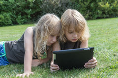 Long haired blond boys are impressed by tablet Stock Photo