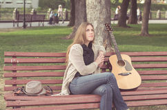 Long-haired blond girl playing an acoustic guitar Stock Images