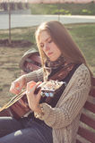 Long-haired blond girl playing an acoustic guitar Royalty Free Stock Photo