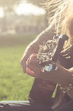 Long-haired blond girl playing an acoustic guitar Stock Image