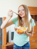 Long-haired blonde girl eating  fruit salad  in home Stock Images