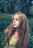 Long haired blonde girl posing in the park looking away retro toned image Royalty Free Stock Photography