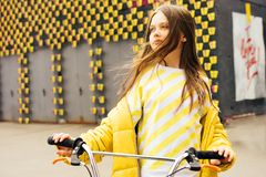 Long-haired blonde girl in a yellow sweater and yellow jacket stock photos