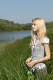 Long-haired blonde on the shore. Royalty Free Stock Images