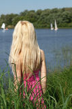 Long-haired blonde on the shore. Stock Images