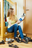 Long-haired blonde woman cleaning footwear Royalty Free Stock Photos
