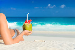 Long haired blonde woman with flower in hair in bikini on tropical beach Stock Photos