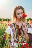 Long-haired blonde young woman in a white short dress on a field of green wheat and wild poppies royalty free stock images