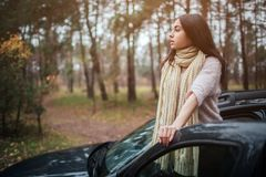 Long-haired brunette on the auto background. A female model is wearing a sweater and a scarf. Autumn concept. Autumn. Forest journey by car Royalty Free Stock Images
