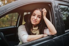 Long-haired brunette on the auto background. A female model is wearing a sweater and a scarf. Autumn concept. Autumn. Forest journey by car Royalty Free Stock Image