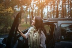 Long-haired brunette on the auto background. A female model is wearing a sweater and a scarf. Autumn concept. Autumn. Forest journey by car Stock Images