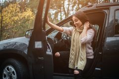 Long-haired brunette on the auto background. A female model is wearing a sweater and a scarf. Autumn concept. Autumn. Forest journey by car Stock Photos