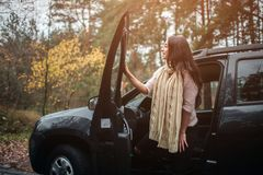 Long-haired brunette on the auto background. A female model is wearing a sweater and a scarf. Autumn concept. Autumn. Forest journey by car Stock Image