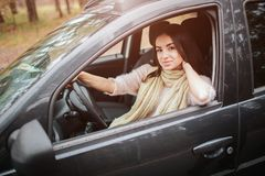 Long-haired brunette on the auto background. A female model is wearing a sweater and a scarf. Autumn concept. Autumn. Forest journey by car Stock Photo