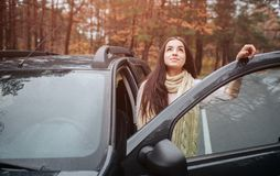 Long-haired brunette on the auto background. A female model is wearing a sweater and a scarf. Autumn concept. Autumn. Forest journey by car Stock Photography