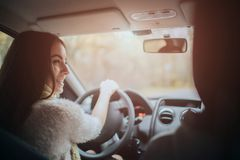 Long-haired brunette on the auto background. A female model is wearing a sweater and a scarf. Autumn concept. Autumn. Forest journey by car Royalty Free Stock Photography