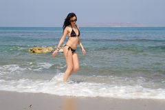 Long haired brunette in black bikini walking at the beach Royalty Free Stock Images