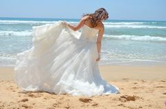 Long-haired brunette bride straightens her dress standing on the sand, the beach on the Indian Ocean. Wedding and honeymoon royalty free stock photo