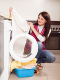 Long-haired brunette girl doing laundry Royalty Free Stock Image