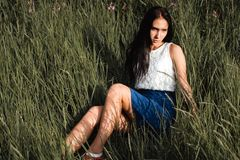 Long-haired teen girl is sitting on grass meadow royalty free stock images