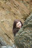 Long haired brunette girl hides behind a rock on a beach royalty free stock photo
