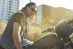Long-haired brunette guy posing on a black custom motorcycle. Long-haired brunette guy in sunglasses jeans and a jeans shirt posing on a black custom motorcycle Royalty Free Stock Photos