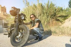 Long-haired brunette guy posing on a black custom motorcycle. Long-haired brunette guy in sunglasses jeans and a jeans shirt posing on a black custom motorcycle Stock Photo