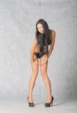 Long haired brunette posing in studio on gray Stock Images