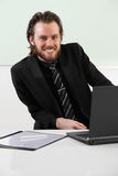 Long haired businessman sitting in a board room Royalty Free Stock Image