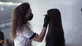 Long haired caucasian beautician is applying dark paint on brows of young woman by brown dye, coloring procedure in a. Beauty studio, close-up, side view stock footage