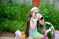Long-haired child girl drinks while riding bike Royalty Free Stock Photography