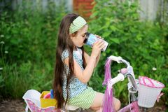 Long-haired child girl drinks while riding bike Stock Photo