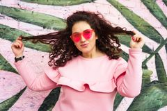 Long haired curly brunette woman in pink dress and pink glasses stock photos