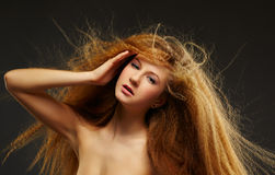 Long-haired curly redhead woman Royalty Free Stock Image