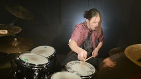 The long-haired drummer finishes playing the drum set in a dark room on a black background. Rock musician. Static plan. Wide angle stock video
