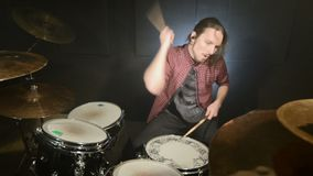 A long-haired drummer starts playing a drum kit in a dark room against a black background. Rock musician. Static plan. Wide angle stock video footage