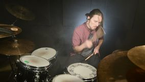 A long-haired drummer starts playing a drum kit in a dark room against a black background. Rock musician. Static plan. Wide angle stock footage