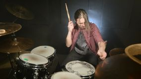Long-haired drummers play drum kit in a dark room on a black background. Rock musician. Static plan. Wide angle.  stock video footage