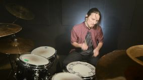 Long-haired drummers play drum kit in a dark room on a black background. Rock musician. Static plan. Wide angle.  stock footage