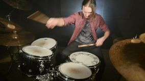 Long-haired drummers play drum kit in a dark room on a black background. Rock musician. Static plan. Wide angle.  stock video